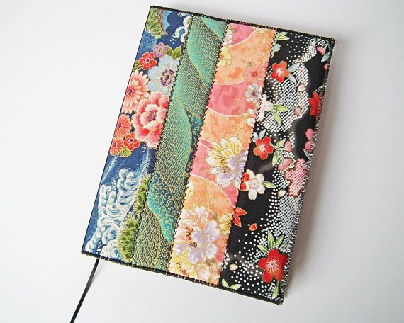 This removable A5 notebook or journal cover is made from a patchwork of strips of assorted Japanese cotton print fabrics, with a textured cotton print lining. The cover is lightly padded and interfaced, with decorative machine stitching along the patchwork seams, oversewn edges, black grosgrain ribbon along the spine, and a narrow black ribbon as an attached bookmark. It comes with a lined, hardback Venetian A5 notebook, which is a totally carbon neutral product. The notebook has 160 pages…