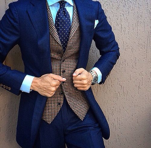 Shop+this+look+on+Lookastic:  https://lookastic.com/men/looks/suit-waistcoat-dress-shirt-tie-pocket-square-watch/13021  —+Aquamarine+Dress+Shirt+ —+Light+Blue+Pocket+Square+ —+Navy+Polka+Dot+Tie+ —+Brown+Houndstooth+Wool+Waistcoat+ —+Silver+Watch+ —+Navy+Suit+