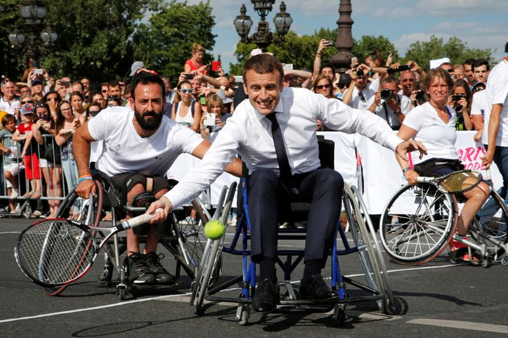 24 June 2017 - French President Emmanuel Macron returns the ball while sitting in a wheelchair as he plays tennis on the Pont Alexandre III in Paris. The French capital was transformed into a giant Olympic park to celebrate Internat'l Olympic Days, w/ a variety of sporting events put on for the public across 2 days. Paris is bidding to host the 2024 Olympic & Paralympic Games | Photo by Jean-Paul Pelissier / Reuters