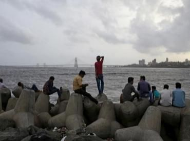 People rest on tetrapods along the Arabian Sea against the backdrop of monsoon clouds in Mumbai