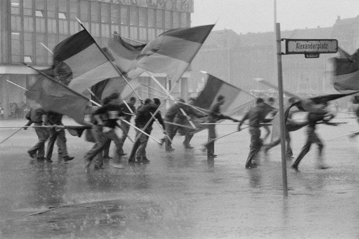 Young men in a rainstorm with German flags at Alexanderplatz Square in East Berlin.