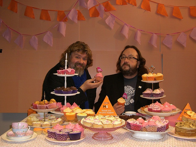Surrounded by cakes!    Si and Dave surround themselves with cakes as part of the photoshoot. You can find out more on next year's Cake Break at www.mssociety.org.uk/cakebreak.
