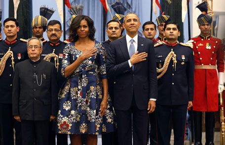 US President Barack Obama and first lady Michelle Obama place their hands over their hearts during the playing of the US National Anthem at a receiving line with India's President Pranab Mukherjee (front L) before the start of an official Indian State Di