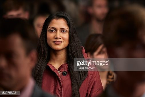 Stock Photo : Portrait of woman standing in crowd & smiling