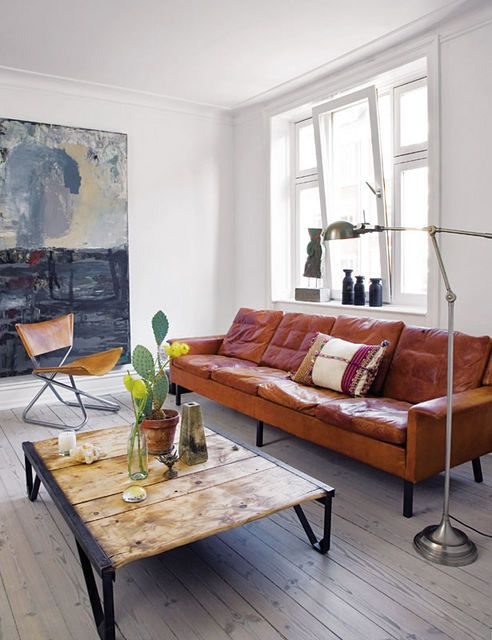 the rustic worn brown leather couch, salvaged wood coffee table, cool metal and leather chair, fantastic floor, and topped off with a cactus? eclectic with a touch of boho living room. beautiful and masculine, with a warm and inviting edge.