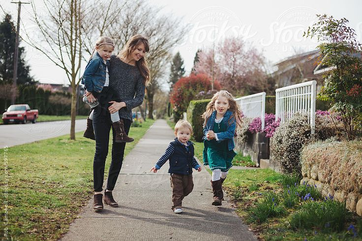 Young mom walking with three kids on sidewalk smiling by Rob & Julia Campbell