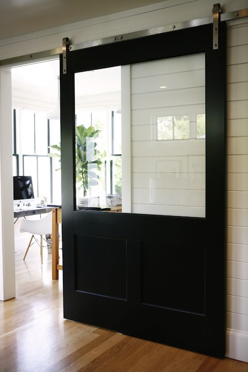 Hallway to home office features tongue and groove paneling framing black sliding barn door with glass window.
