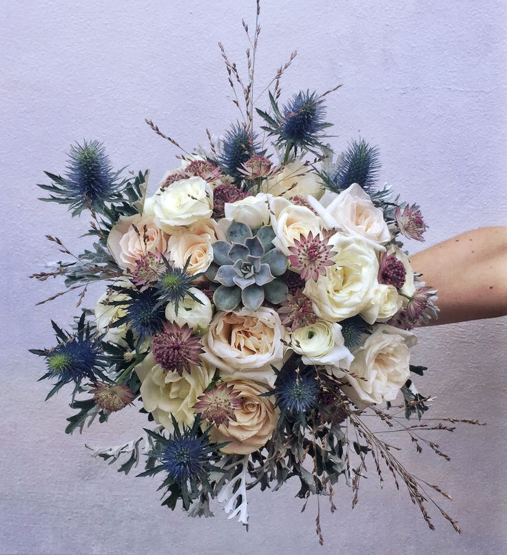 Bridal flowers with a Celtic twist. Roses, Astrantia, Sea holly & succulent bouquet for a winter wedding.