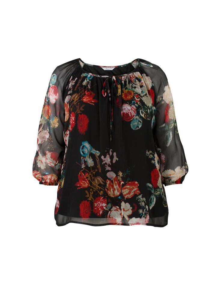 Gebloemde blouse met driekwart mouwen en een ronde hals met elastiek en koordjes. De bovenste stof is voile. Het is een licht getailleerd model, gemaakt van polyester kwaliteit. Heuplengte.