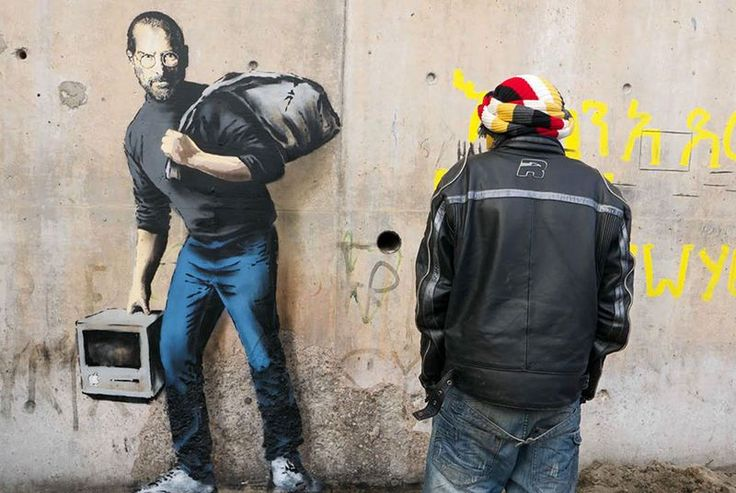 "New Bansky piece puts Steve Jobs in a Syrian refugee camp Anonymous street artist Banksy is bringing awareness to the Syrian refugee crisis. The British artist spray painted an image of Steve Jobs the child of a Syrian refugee on a wall in Frances infamous Calais refugee camp. Banksy painted Jobs standing with an original Mac in one hand and a sack over his shoulder. The caption ""the son of a migrant from Syria"" accompanies a photograph of the work on Banksy's website.  Continue reading"