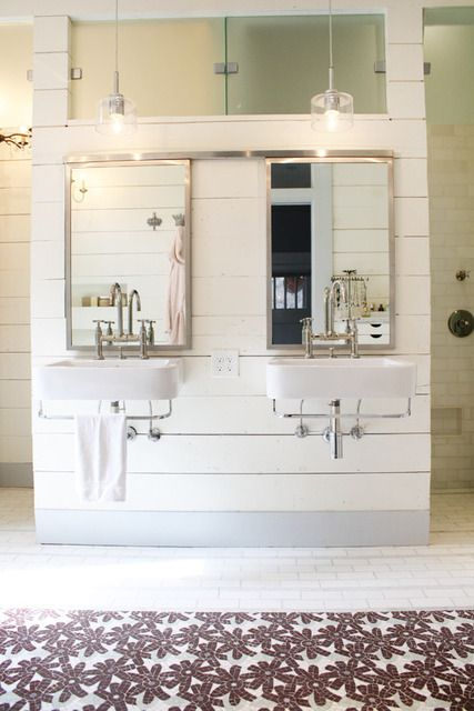 LOVE. Two sinks and mirrors on a short wall with clerestory window above and doorways on each side that open to the walk-in shower. Also, the style. There are tiny corner vanities  mirror/medicine cabinets at the far side of each doorway.