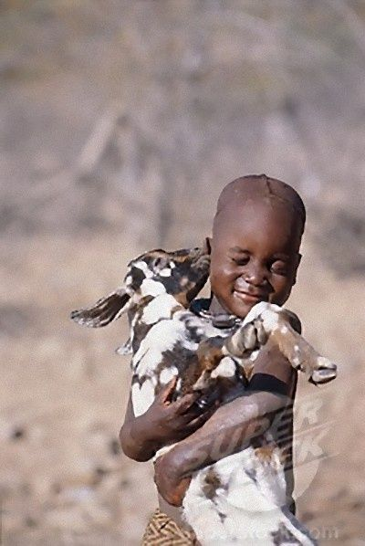 """""""Kiss, kiss"""" -- A Himba boy in Namibia, Africa gets a sweet smooch from his pet goat."""