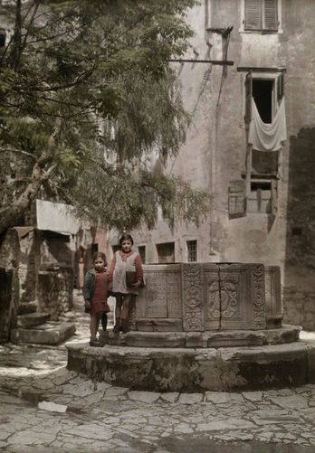 Autochrome: Wilhelm Tobien. Two children stand next to an old Venetian well. Kerkira (Corfu City), Kerkira Island (Corfu Island), Ionian Islands, Greece. 1920s - 1930s.