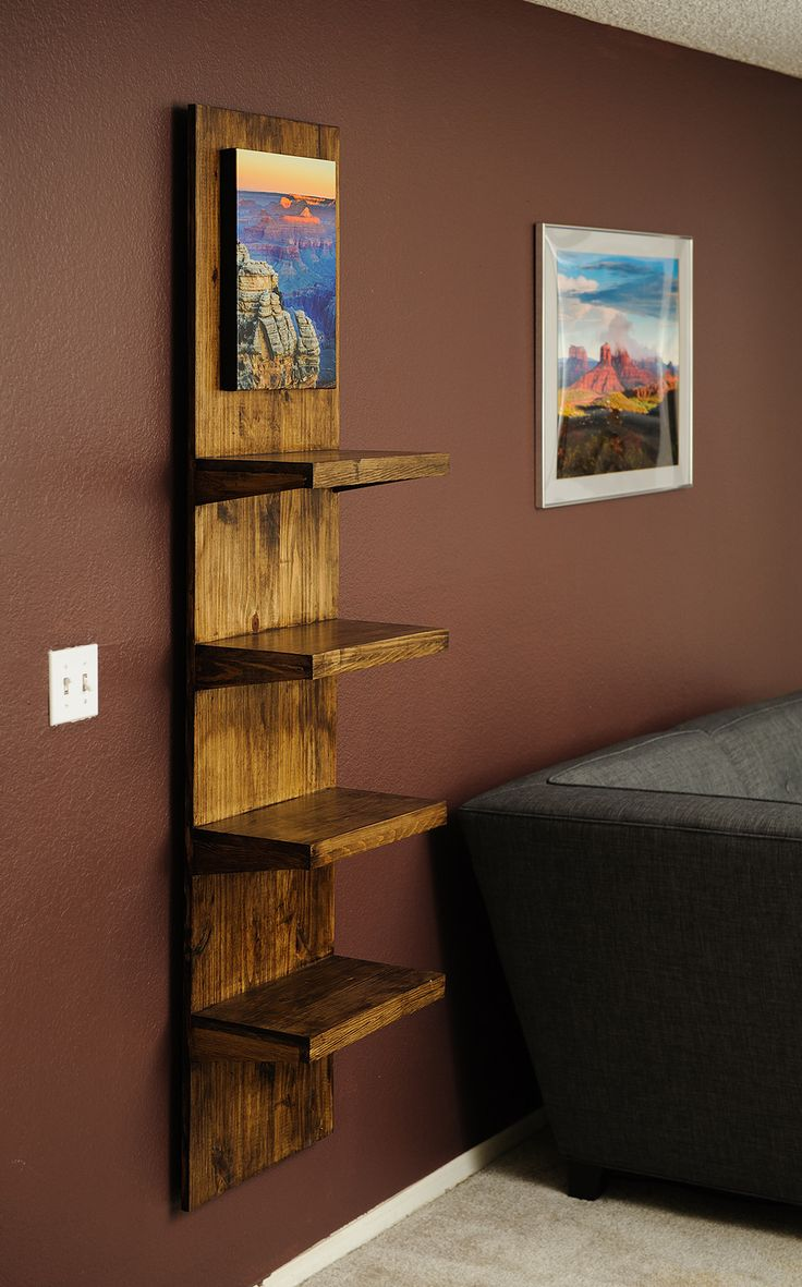 a vertical wall shelf with a canvas picture on top. interesting; idea for sure.