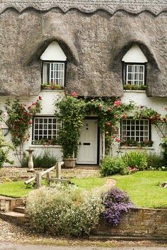 English Cottage.  I think the 2nd floor windows have 'eyebrow' roofs over them.