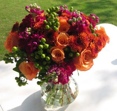 Fall orange roses, magenta stock, orange mums and green hypericum arranged in a European wrap style.
