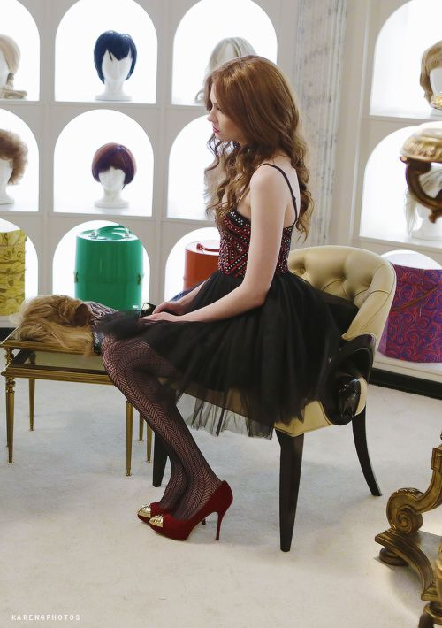 Karen Gillan in Selfies. Black and red dress, patterned tights, and red heals