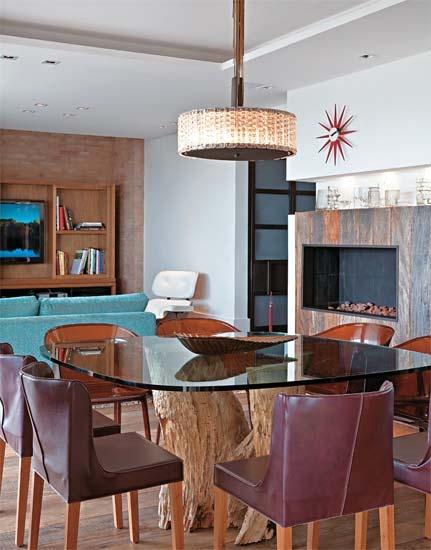 A mesa de jantar com base de tora de Angelim certificado ganhou um tampo de vidro com cantos arredondados. Ao redor do móvel, alternam-se cadeiras de couro (Dpot) e acrílico marrom (Kartell). Centro de mesa e lustre de estilo retrô da Galeazzo Design.