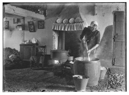 """Het interieur van boerderij """"de Uiltjes"""", in Zevenend - Zevenenderdrift te Laren (NH) De vrouw in klederdracht aan de wastobbe is Klaasje Calis, zij was getrouwd met Klaas Koppel. Haar gesteven kapje heet een """"Utrechtse Hul"""", dat voornamelijk op zondag werd gedragen door rooms-katholieke vrouwen in de dorpen Laren, Blaricum en Eemnes. 1907-1920 Gemeente Amsterdam Stadsarchief Bernard F. Eilers #NoordHolland #Gooi #Laren #rond"""