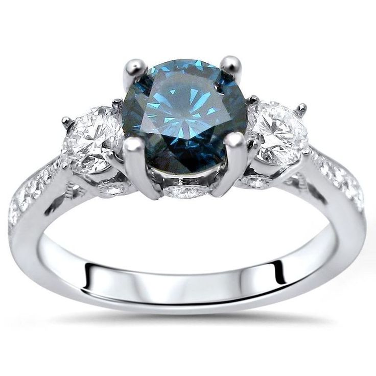 A beautiful round cut blue diamond sits between two white diamonds on a 14-karat white gold band, contrasting brilliantly.  Glamorous and elegant, this original engagement ring will stand out among the rest.
