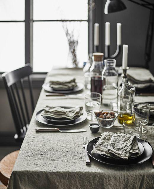 Un tavolo da pranzo rustico moderno con una tovaglia in lino, un mix di sedie diverse e stoviglie moderne - IKEA