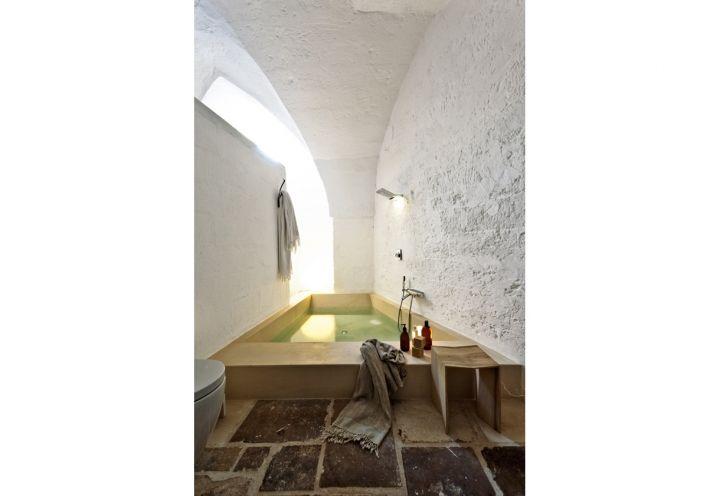 Per la vasca in pietra, realizzata su misura da Pimar, rubinetteria Zucchetti. Pavimento di vecchie pietre recuperate nel frantoio