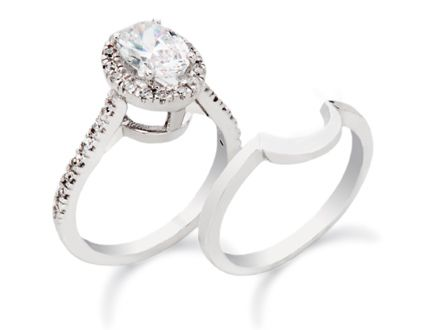 White gold engagement ring featuring an oval cut center diamond, round melee and a matching wedding band