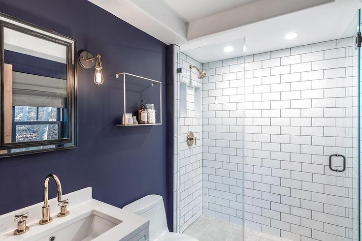 Deep blue walls set a soothing tone in Nate and Michelle's downstairs bath while the white ceiling and subway tile keeps the space feeling bright.
