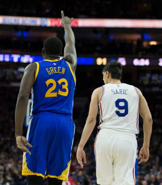 Draymond Green of the Golden State Warriors reacts in front of Dario Saric of the Philadelphia 76ers in the fourth quarter at the Wells Fargo Center...