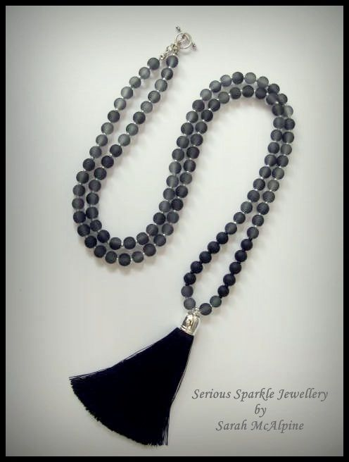 This stunning necklace is handmade from gorgeous grey frosted glass beads with tiny silver glass bead spacers and black frosted glass bead accents. At the end hangs a luscious, soft black silk tassel hanging from a silver cap.    The necklace fastens with a silver toggle clasp and measures 8cm in length. The tassel is 8cm long.