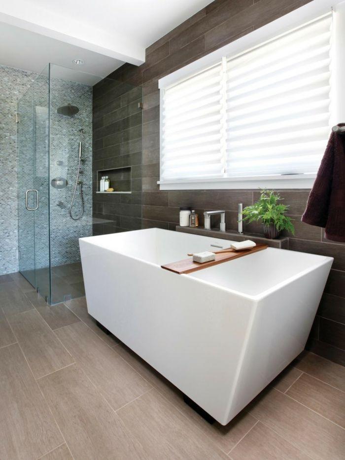 Bad, Bodenebene Dusche mit Ablagefach, Duschtrennwand Glas, Freistehende Badewanne, Fenster über Badewanne, Bodenfliesen in Holzoptik, Wandfliesen braun, Mosaik grau