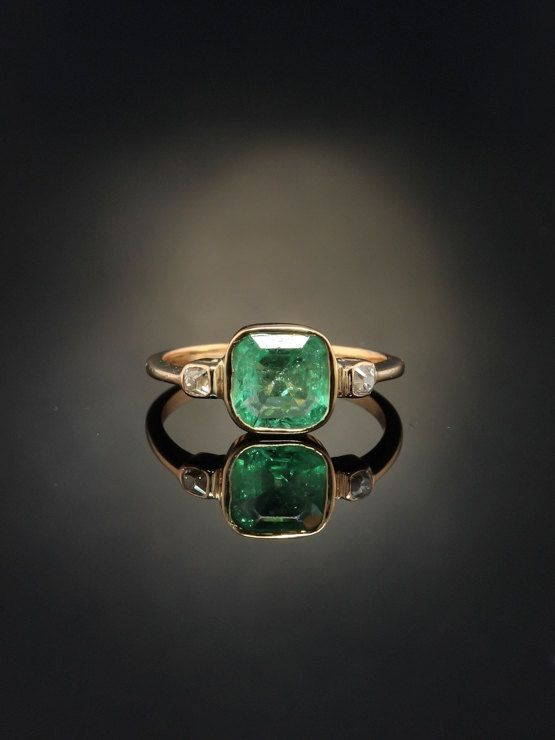 History and meaning Jewelry fro Georgian era carries such a distinctive air, with the stories they could tell, the changes they have witnessed. Now onto a new life. Graciousness for Georgian jewelry is represented in this gorgeous natural emerald and diamond trilogy ring bringing with it meaning and drama. Within the warmth of antique gold a crystal green natural emerald settles in repose amidst the embrace of rubover mounting, kissed by two sparkling romantic old mine cut diamonds on sid...