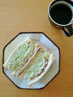 《元祖・沼サン》 by 大沼由樹 [クックパッド] ■材料 6枚切り食パン2枚 キャベツ140g 玉ねぎ20gベーコン1枚 とけるスライスチーズ1枚 マヨネーズ大さじ2~2+半 粒マスタード適量 ■作り方  ①食パンの1枚にチーズとベーコンをのせ、もう1枚はそのままで両方トーストする。チーズの上にベーコンをのせるとサンドするときにはがれにくくなる。こんがり焼き目が出るまで焼く ②サンドする具をつくる。キャベツ千切りと玉ねぎスライス、好みでオリーブやピクルスのみじん切りをマヨネーズとブラックペッパーであえる ④パンが焼けたら何ものっていない方に粒マスタードを塗る。好みでアボカドスライスものせる ⑤具を山盛りにのせて、ベーコンチーズをのせたパンでサンドし、半分にカットしてできあがり。※マヨネーズで和えるのはのせる直前するのがコツ http://cookpad.com/recipe/3417587