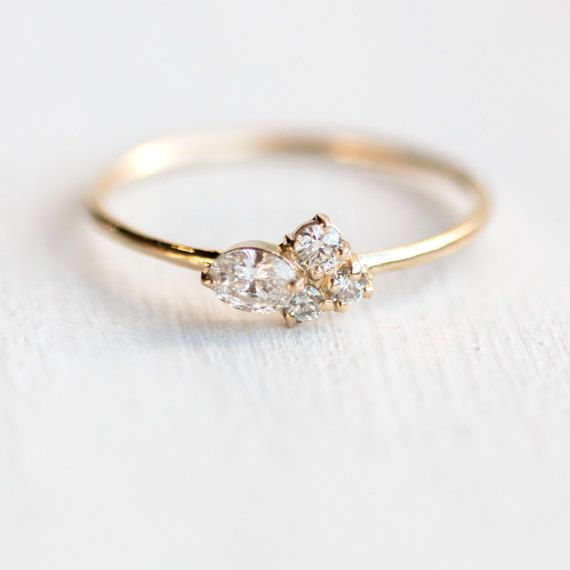 This delicate mini cluster ring features a cluster of four sparkling genuine white diamonds in prong setting, on top of a very delicate smooth slim band. This handmade asymmetrical cluster ring will be a great everyday ring or elegant simple engagement ring. ♦ Solid 14k gold (available in white, yellow, or rose) ♦ One oval white diamond (3x4mm, SI2 or better clarity, G or better color, approx. .15 carat) ♦ One 2.5mm white diamond (I2 clarity, G-H color) ♦ Two 2mm white diamonds (I2…