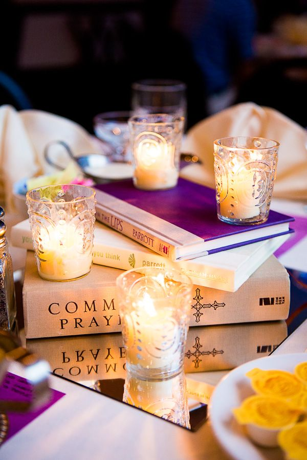 love book centerpieces = books and candles. the books add dimension