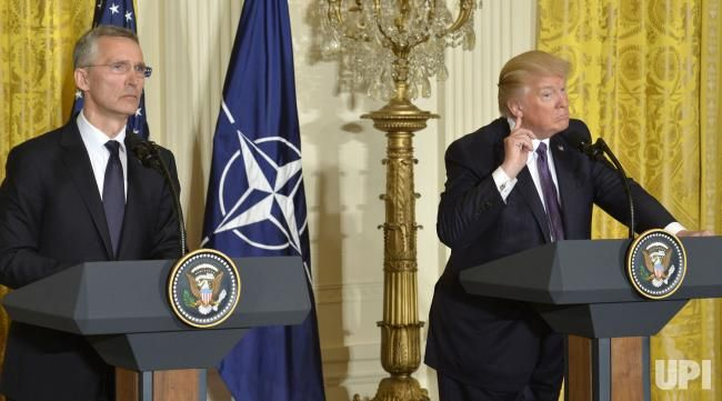 President Donald Trump (R) cups his ear to hear a reporter's question as NATO Secretary General Jens Stoltenberg listens during a news…