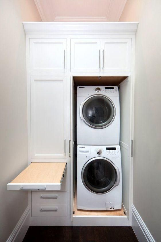 No Space Too Small - 10 Laundry Room Ideas We're Obsessed With - Southernliving. This stacker washer and dryer set wastes no space. The surrounding cabinetry disguises the laundry station, keeping necessary products and tools hidden. Plus, a surprise pullout folding board!  See Pin