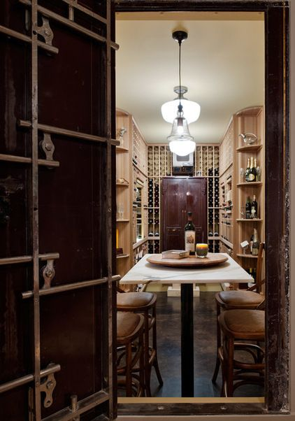 absolutely awesome contemporary wine cellar -- love the bank vault door and tasting table!