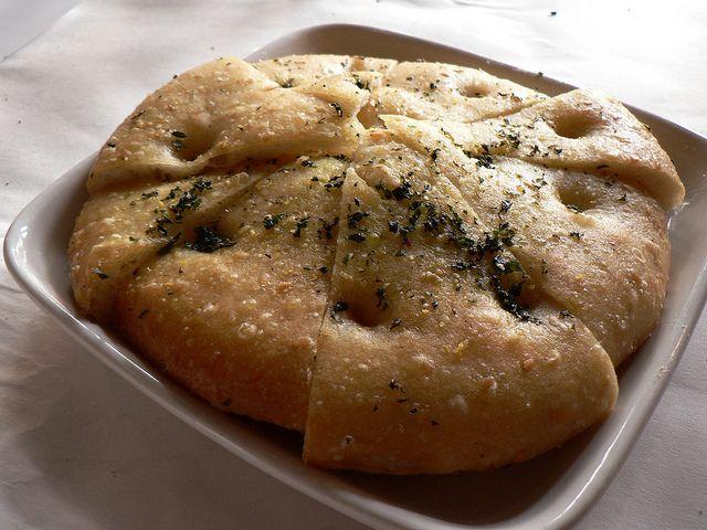 La focaccia Bimby è un impasto semplice e genuino a base di farina, acqua, lievito e sale, simile a quello del pane, cotto al forno o alla brace.