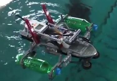 This Mindstorms paddleboat was built by Mike and Cedric of the OSZT school in Täuffelen, Switzerland. Looks like it sports a regular Lego ship base with soda bottles as pontoons. A pair of paddlewh...