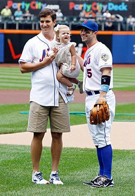 New York Giants quarterback Eli Manning holds his daughter Eva while posing with New York Mets third baseman David Wright before the game against the Cincinnati Reds at Citi Field on June 17, 2012.