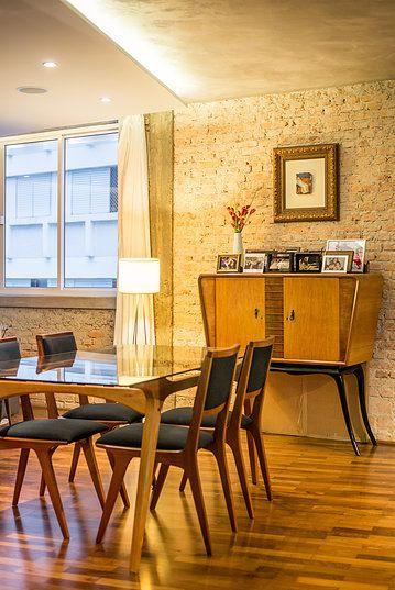 Sala de jantar. Piso de tacos de madeira, parede de tijolinhos originais descascados e pilar em concreto aparente, cimento queimado no teto, iluminado por fita LED em sanca no forro de gesso.