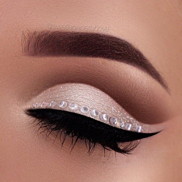 Black eyeliner line with beautiful rhinestones above eyeliner gives a beautiful and glamorous look. Lighter shadow on the lower eyelid should always be framed – contoured with darker in this case brown shadow to give the best look.