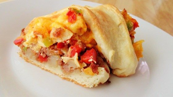 A crescent roll ring is filled with corned beef hash, scrambled eggs with peppers, and shredded Cheddar cheese.