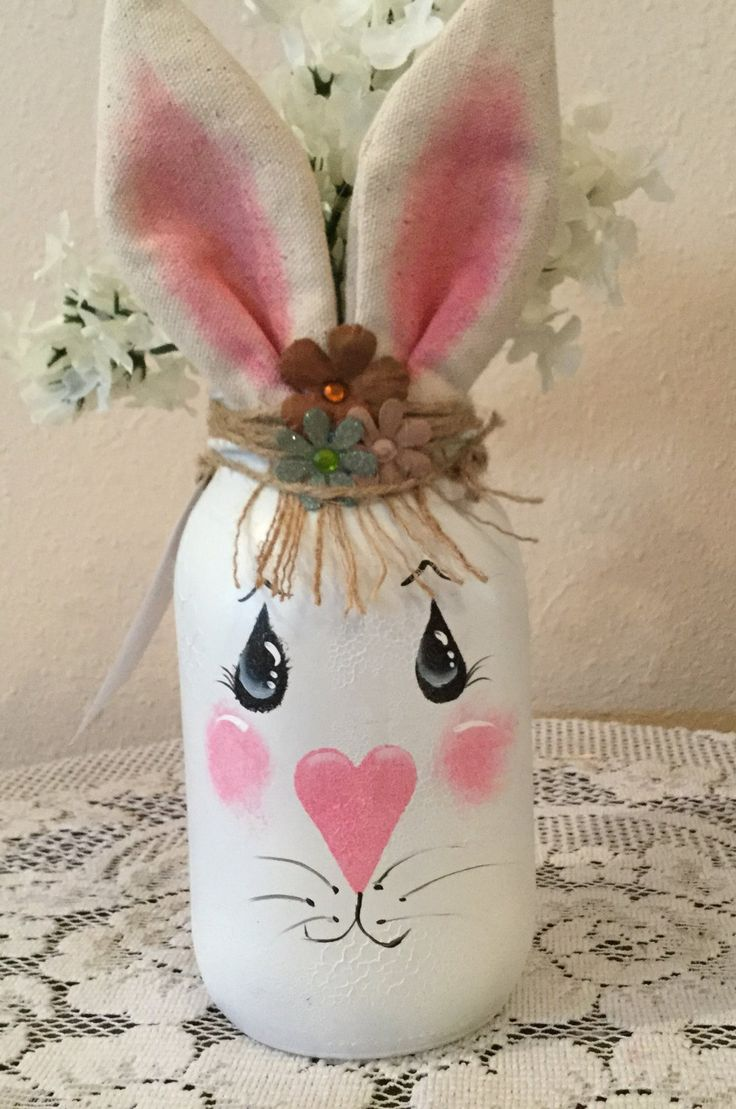 These quart size jars have been painted white, distressed and a sweet rabbit face has been painted on the front. She has Jute hair and fabric ears. Faux flower has been added to the top of her head. Flowers will vary as well as the flowers inside the jar depending on availability.