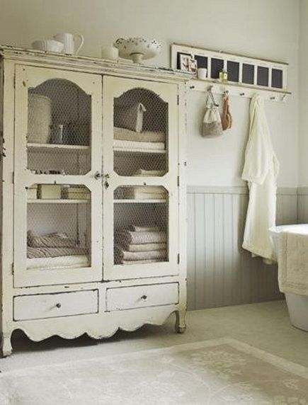 cottage bathroom with large white storage armoire
