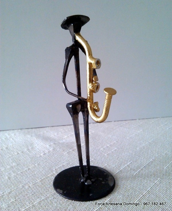 Figura de forja de un musico tocando el saxofon, hecha a mano de forma artesana.