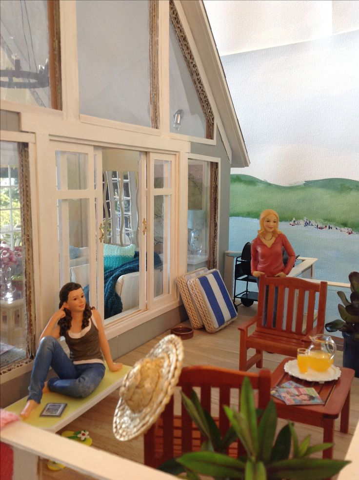 Beach house 1/12 scale. Dolls house family on the veranda enjoying the sea view