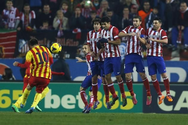 Barcelona's Lionel Messi from Argentina, left, takes a free kick as, from left to right,  Atletico's,Tiago, Diego Costa, Gabi, and D...