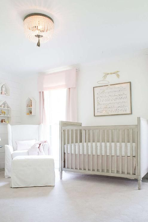 Beautifully appointed gray and pink nursery features a RH Baby & Child Scallop Wool Rug placed under a Restoration Hardware Baby & Child Marcelle Crib positioned beneath a Antique Sheet Music - Hush Little Baby framed piece hung on a wall beside a window dressed in Cotton Canvas Drapery Panels in Petal located behind a catty corner Wingback Slipcovered Swivel Glider & Ottoman illuminated by a Dauphine Pendant.
